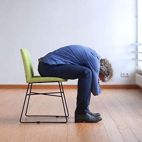 Pavan-Muktasana (wariant na krześle) pozycja jogi do wykonania przy biurku w pracy