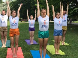 Ludzie w parku uprawiający jogę dynamiczną